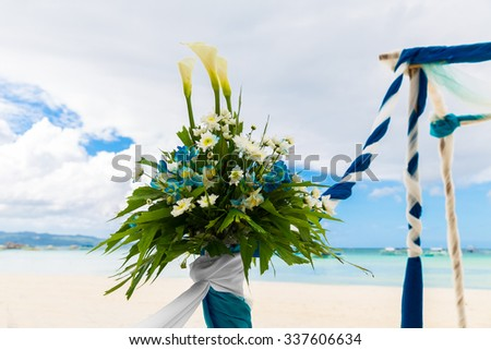 Wedding ceremony on a tropical beach in blue. Arch decorated with flowers on the sandy beach. Wedding and honeymoon concept.