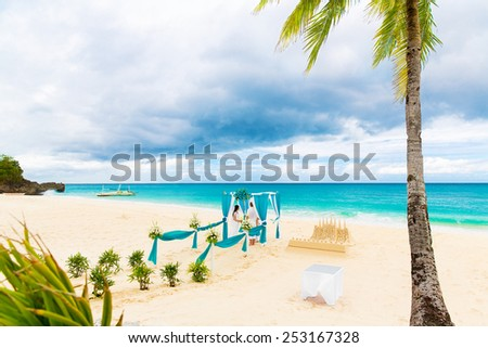 Wedding ceremony on a tropical beach in blue. Wedding arch decorated with flowers on tropical sand beach under the palm tree.  - stock photo
