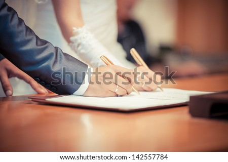 Wedding ceremony. Wedding couple leaving their signatures - stock photo