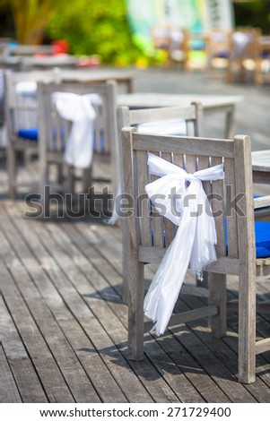 Wedding chairs decorated with white bows at outdoor cafe - stock photo