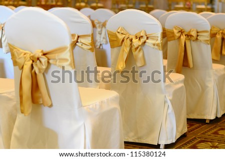 Wedding chairs in row decorated with golden color ribbon. - stock photo