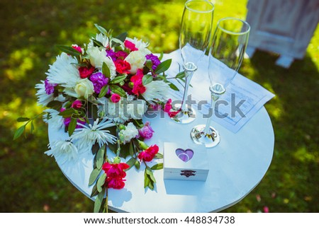 Wedding champagne flutes stand on the round table outside