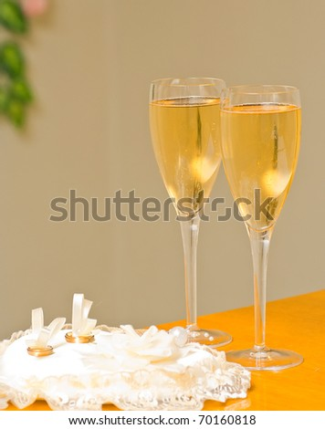 wedding champagne glasses and wedding rings - stock photo