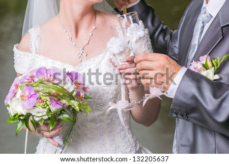 Wedding champagne glasses in hands of groom and bride