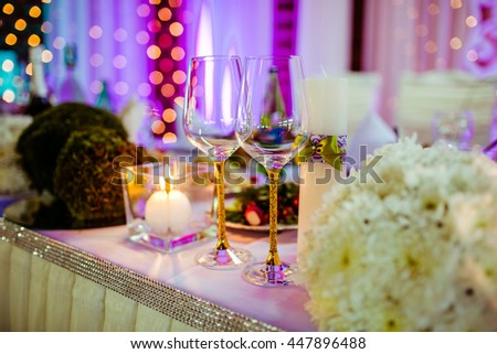 Wedding champagne glasses with golden design stand on the dinner table