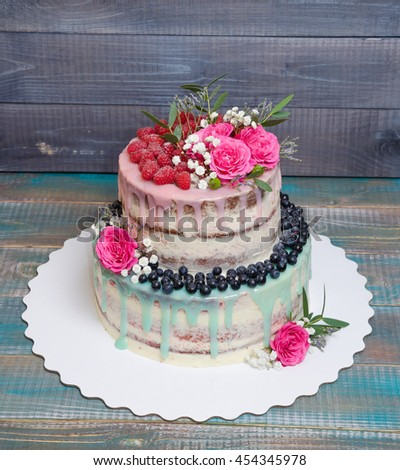 wedding color drip cake with roses, blueberries and  raspberries on wooden plank