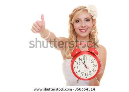 Wedding concept. Time to get married. Happy bride with red alarm clock showing thumb up hand sign gesture. Beautiful blonde woman waiting for the groom isolated on white