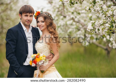 wedding copule. Beautiful bride and groom. Just merried. Close up. Happy bride and groom on their wedding hugging. Groom and Bride in a park. wedding dress. Bridal wedding bouquet of flowers - stock photo