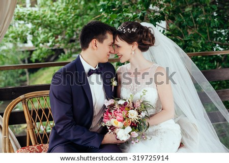 wedding copule. Beautiful bride and groom. Just merried. Close up. Happy bride and groom on their wedding hugging. Groom and Bride in garden. wedding dress. Bridal wedding bouquet of flowers - stock photo