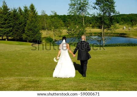 Wedding couple are walking in park.