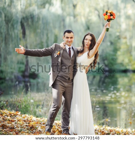 Wedding couple at countryside next to forest lake.  Groom and bride together.