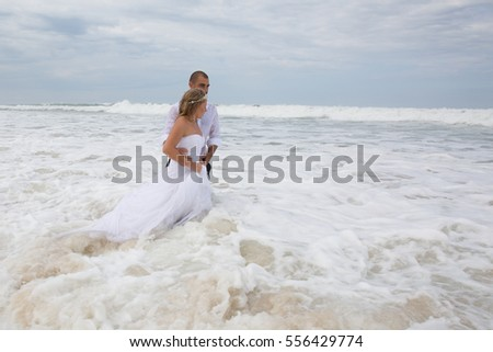 Wedding couple at the beach with a wedding clothes in marriage day