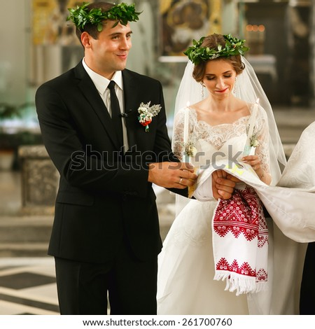 wedding couple at the ceremony with candles and wreaths