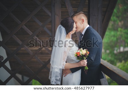 wedding couple, beautiful young bride and groom standing in a park outdoors holding hands and smiling