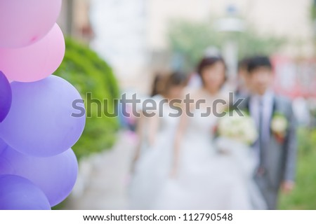 Wedding couple behind bunch of colorful balloons