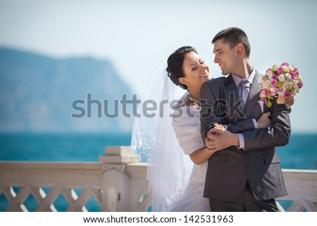 Wedding couple bride and groom on sea beach newlywed man and woman outdoors near ocean. Happy loving couple in wedding day embracing on nature. Romantic relationship. wed couple with bouquet flowers.