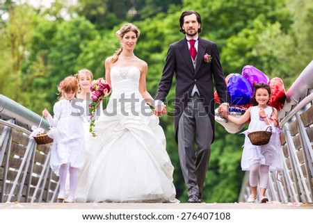 Wedding couple bride and groom with flower children or bridesmaid in white dress and flower baskets - stock photo