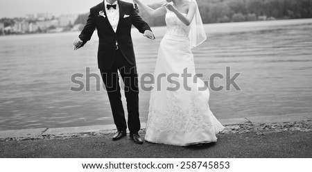 Wedding couple dancing by the lake. Newlyweds just having fun.