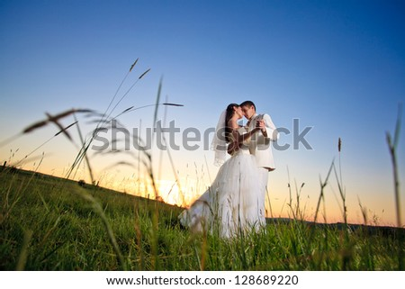 Wedding couple dansing in mountain hill on sunset - stock photo