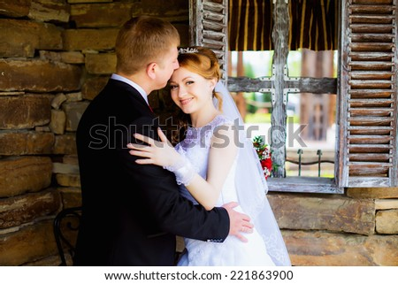 Wedding couple embracing on a background of a stone wall and window