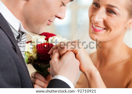 Wedding couple giving promise of marriage; the groom is kissing the hand of his bride