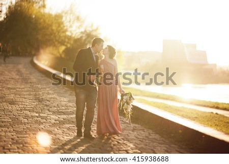 Wedding couple, groom and dress posing near river with a glass at sunset