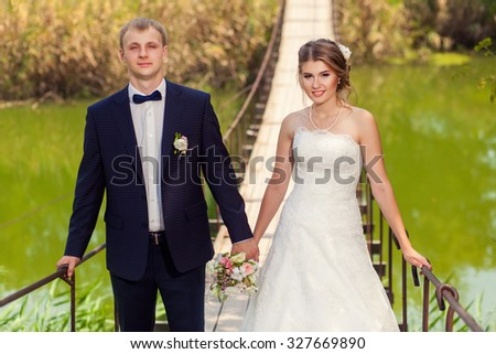 Wedding couple hand in hand on suspension bridge