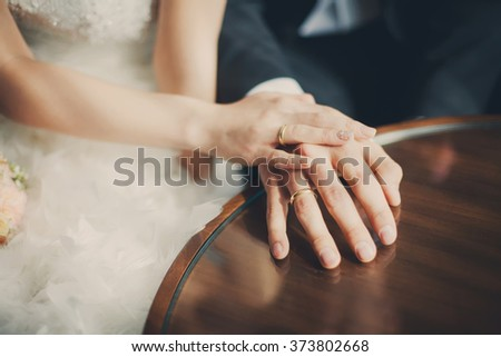 Wedding couple hands closeup with golden rings laying at the table at wedding day celebration - stock photo