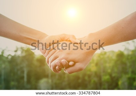 Wedding couple holding hands against sunrise over garden - stock photo