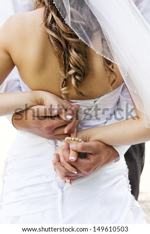 Wedding couple holding hands and hugging.