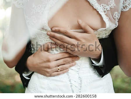 Wedding couple holding hands and hugging body part - stock photo