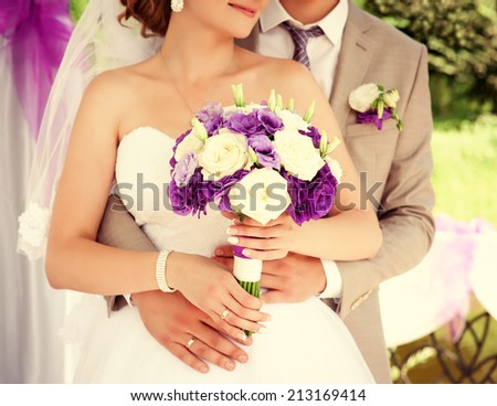 Wedding couple holding hands. Bride and groom holding hands. Wedding bouquet closeup. Fashionable toning. Wedding invitation, Selective focus  - stock photo