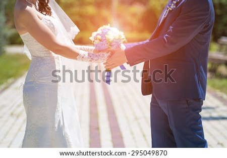 Wedding couple holding hands in sunny wedding day - stock photo