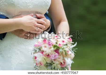 Wedding couple holding hands on summer green background with Rich bunch of pink peonies and lilac eustoma roses flowers. Wedding concept with bouquet and copy space for text