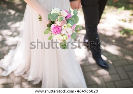 Wedding couple holding hands on summer green background with Rich bunch of pink peonies and lilac eustoma roses flowers. Wedding concept with bouquet