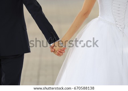 Wedding couple holding hands outdoor close up. Family concept.