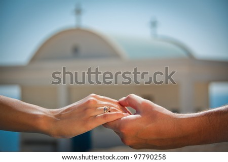 Wedding couple holding hands with golden rings on a church background. - stock photo