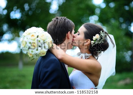 wedding couple hugging and kissing in a private moment - stock photo