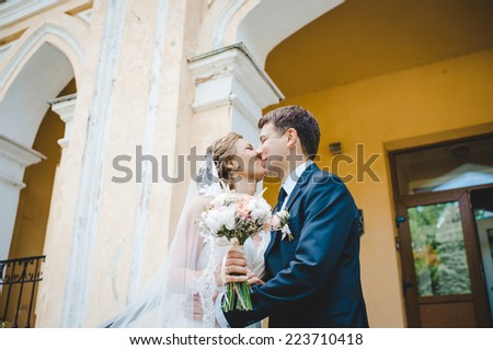 wedding couple hugging and kissing in a private moment near old building