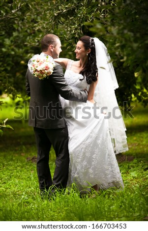 Wedding couple hugging and looking at each other at garden under trees