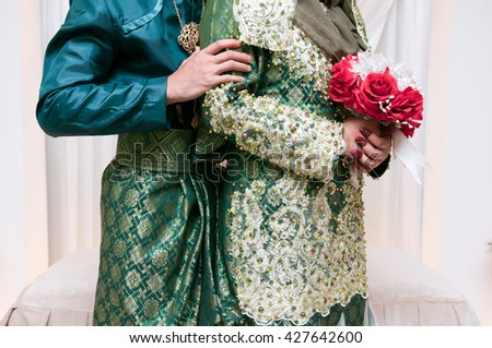 Wedding couple hugging, the bride holding a bouquet of flowers in her hand, groom embracing. - stock photo