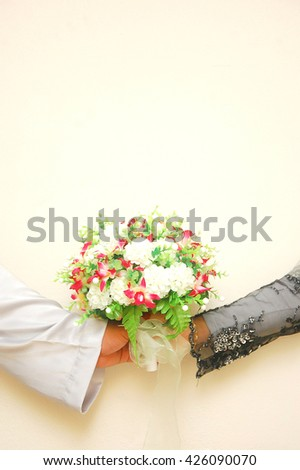 Wedding couple hugging, the bride holding a bouquet of flowers in her hand, groom embracing.copy space text - stock photo