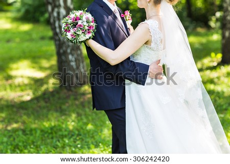 wedding couple hugging, the bride holding a bouquet of flowers in her hand, the groom embracing her - stock photo