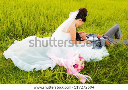 wedding couple hugging, with a bouquet of flowers - stock photo