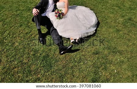 Wedding couple in garden sitting on grass,  bride and groom together