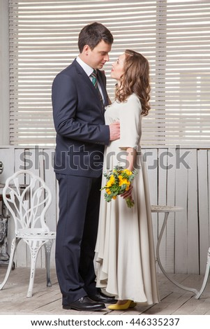 Wedding couple in love. Beautiful bride in white dress and handsome groom in black suite standing and embracing each other in studio.