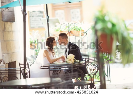 Wedding couple in love. Beautiful bride in white dress and veil and brides bouquet with handsome groom in blue suit sitting in cafe. Full lenght portrait of man and girl. Concept of wedding - stock photo