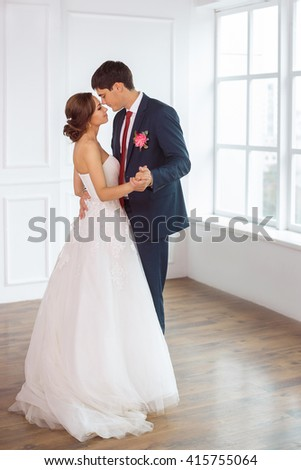 Wedding couple in love. Beautiful bride in white dress with brides bouquet and handsome groom in blue suite standing and embracing each other indoors in decorated studio room, white bright interior - stock photo