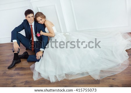 Wedding couple in love. Beautiful bride in white dress with brides bouquet and handsome groom in blue suite sitting on the floor and embracing each other indoors in decorated studio room, white bright