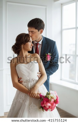 Wedding couple in love. Beautiful bride in white dress with brides bouquet and handsome groom in blue suite standing and embracing indoors in decorated studio room, white bright interior with big - stock photo